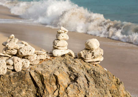 Multiple stacks of pebbles on rock by sea shore with sun lighting the piles Imagens