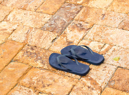 pool deck: Discarded childs blue flip flops on paved deck by swimming pool with water in indentations
