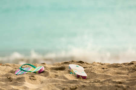 flops: Discarded childs flip flops on sandy beach by turquoise ocean in sun