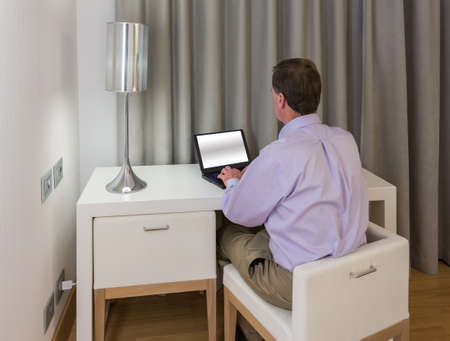 Senior man at modern white table desk and two chairs in hotel room at night photo