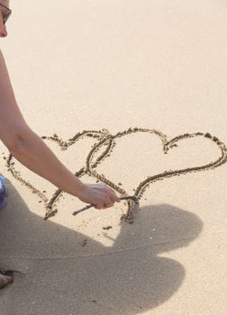 linked: Lady drawing pair of linked hearts in sand on beach in Caribbean