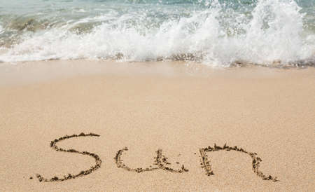 sand writing: Sand drawing on warm beach by ocean surf in Caribbean spelling Sun