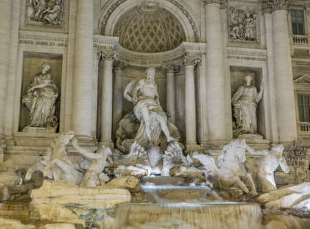 bernini: Night time floodlit details of statues in Trevi fountain in Rome Italy