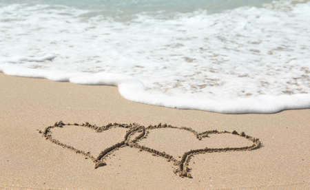 linked: Sand drawing on warm beach by ocean surf in Caribbean with linked hearts