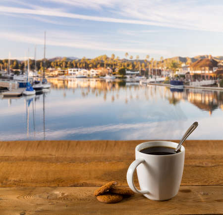 Coffee cup and biscuits on wooden table or deck by luxury harbor with expensive homes photo