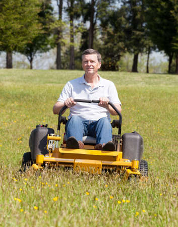 cut grass: Senior retired male cutting the grass on expansive lawn using yellow zero-turn mower