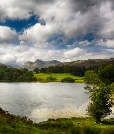 langdale pikes: Sun illuminating Langdale Pikes with Loughrigg Tarn in foreground