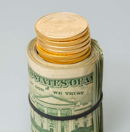 Gold coins standing on roll of many $20 dollar bills and notes secured by elastic band on white table Stock Photo