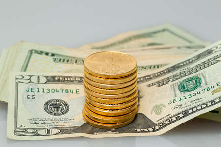 bankroll: Gold coins standing on many $20 dollar bills and notes on white table