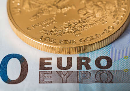 Solid gold coins contrasted with euro notesuggesting debt problems in Europe photo