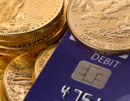 chip and pin: Solid gold coins contrasted with debit word on plastic credit card suggesting debt problems
