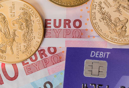 suggesting: Solid gold coins contrasted with debit word on plastic card on euro note suggesting debt problems