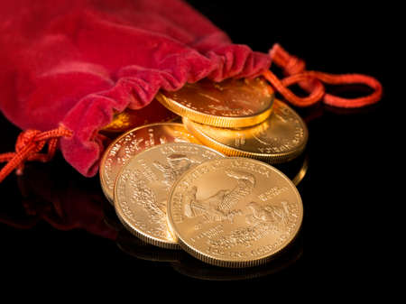 Stacks of gold eagle one troy ounce golden coins from US Treasury mint pouring from mouth of red velvet money bag photo
