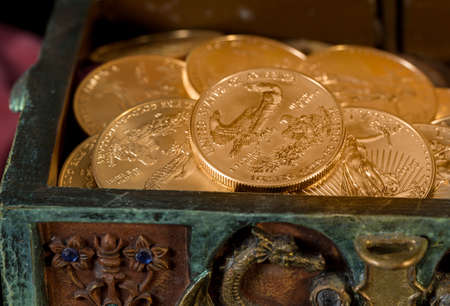 ounce: Stacks of gold eagle one troy ounce golden coins from US Treasury mint in old carved pirate treasure chest