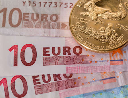 Solid gold coins contrasted with numbers on euro note suggesting debt problems photo