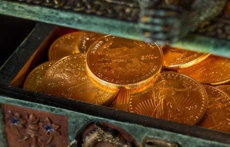 Stacks of gold eagle one troy ounce golden coins from US Treasury mint in old carved pirate treasure chest photo