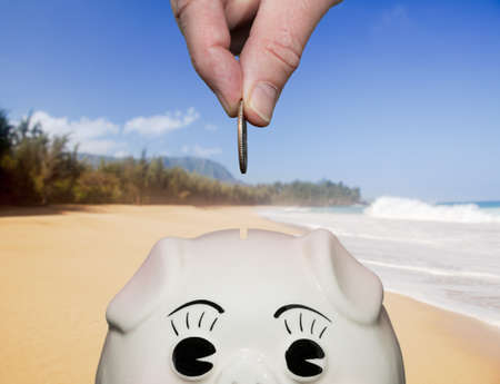 Coin being inserted into piggy bank with fingers illustrating saving for vacation on beach photo