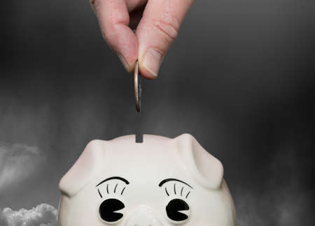 suggesting: Coin being inserted into piggy bank with fingers suggesting saving for a rainy day or stormy weather Stock Photo