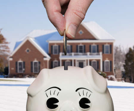 Coin being inserted into piggy bank with fingers suggesting saving for a deposit or mortgage on a home photo