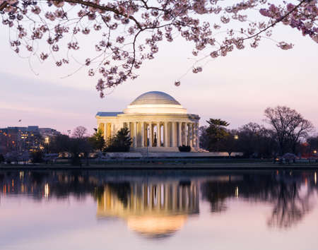 Jefferson Memorial at dawn by Tidal Basin and surrounded by pink Japanese Cherry blossoms with the monument lit by the rising sun at dawn photo