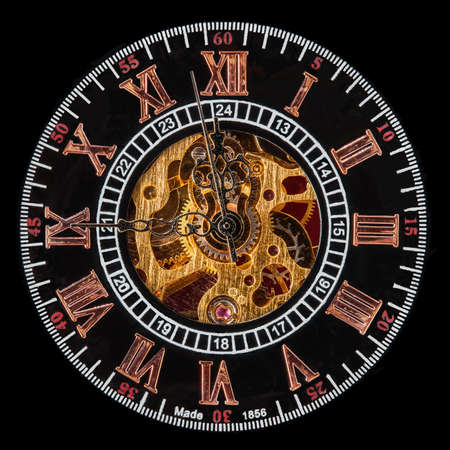 clock: Macro shot of the face of an old pocket watch with a hand-wound mechanical movement. Clock shows hands approaching midnight