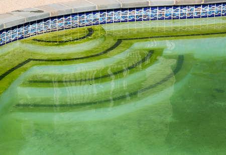 algen: Achtertuin zwembad achter moderne eengezinswoning in zwembad opening met groene stilstaand algen gevuld water voor het reinigen Stockfoto