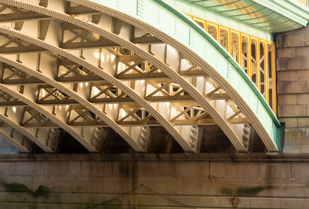 ironwork: Girders supporting Southwark Bridge across the Thames river in London with setting sun lighting the painted ironwork Stock Photo