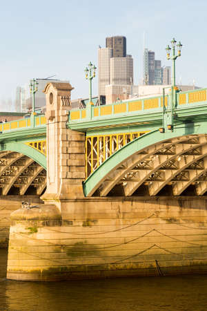 girders: Girders supporting Southwark Bridge across the Thames river in London with setting sun lighting the painted ironwork Stock Photo