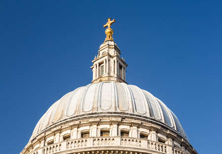 st pauls: Golden cross on dome of St Pauls Cathedral in London England at dusk as the sun is setting low in sky. Stock Photo
