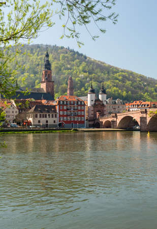 Medieval bridge leading into old town of Heidelberg Germany from riverbank of River Neckar photo