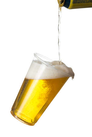 tilting: Golden beer, ale or lager in a tilting plastic disposable cup or glass with beer being poured from can and spilling over edge of pint