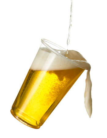 Golden beer, ale or lager in a tilting plastic disposable cup or glass with beer being poured and spilling over edge of pint glass Stok Fotoğraf