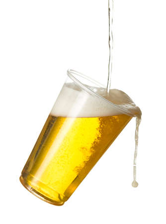 unbreakable: Golden beer, ale or lager in a tilting plastic disposable cup or glass with beer being poured and spilling over edge of pint glass Stock Photo