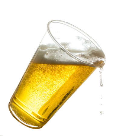 Golden beer, ale or lager in a tilting plastic disposable cup or glass with beer spilling over edge of pint glass Stockfoto