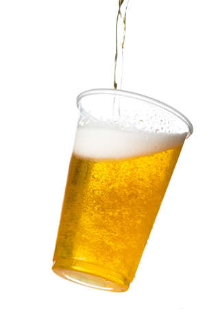 Golden beer, ale or lager in a tilting plastic disposable cup or glass with beer being poured and spilling over edge of pint glass Stock Photo