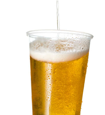 pint glass: Golden beer, ale or lager in a tilting plastic disposable cup or glass with beer being poured and spilling over edge of pint glass Stock Photo