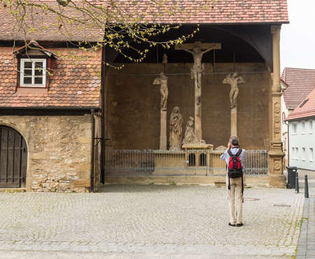 crucifixes: BAD WIMPFEN, GERMANY - APRIL 26: Tourist photographer takes photo of the ancient stone carved crucifixes on April 26, 2013. This Crucifixion group is the work of Mainz sculptor Hans Backoffen in about 1515. Editorial
