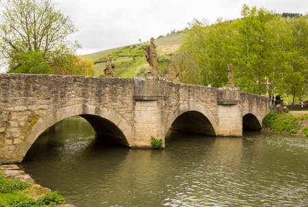 stone bridge: Antique carved statues on old arched bridge across river Grunbach in Southern Germany