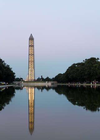 Washington Monument encased in 500 tons of scaffolding to repair damage caused by 2011 Earthquake in Washington DC. Tower illuminated and reflecting in the Reflecting Pond by Lincoln Memorial Zdjęcie Seryjne