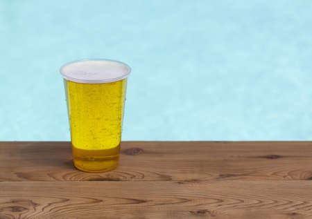 safe water: Golden beer, ale or lager a plastic disposable cup for party on wooden table by swimming pool