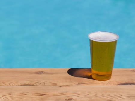 foam safe: Golden beer, ale or lager a plastic disposable cup for party on wooden table by swimming pool