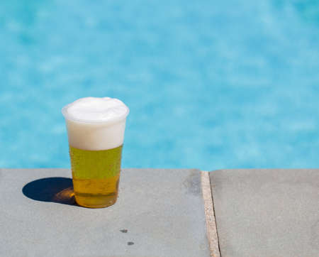 edge: Golden beer, ale or lager in a plastic disposable cup or glass for party by swimming pool