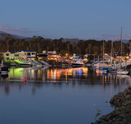 Sunset over residential development by water in Ventura California with modern homes and yachts boats Stock Photo