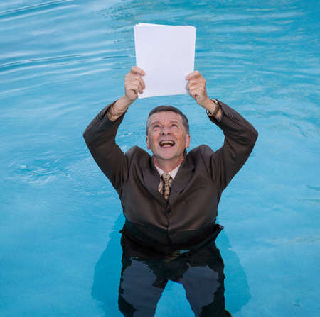 waist deep: Senior caucasian businessman in suit up to waist in deep blue water worried about drowning in paperwork and holding blank document Stock Photo