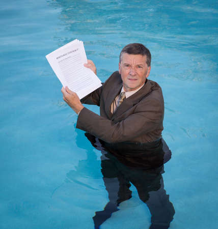 waist deep: Senior caucasian businessman in suit up to waist in deep blue water worried about being underwater with mortgage payments Stock Photo