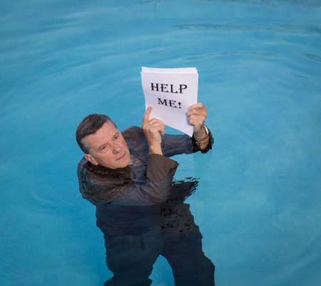 baby boomer: Senior caucasian businessman in suit up to neck in deep blue water worried about drowning in paperwork and holding help me document