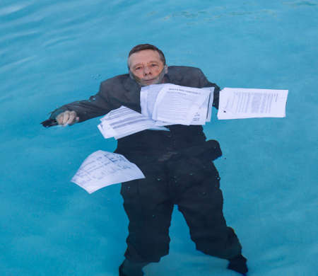 Senior caucasian businessman in suit sinking underwater in deep blue pool worried about being underwater with mortgage payments Archivio Fotografico