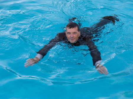 waist deep: Senior caucasian businessman in suit swimming in deep blue water and smiling as he tries to keep afloat Stock Photo