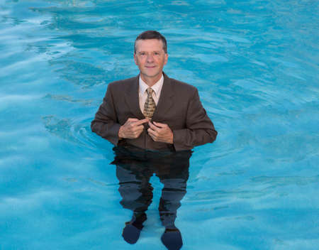waist deep: Senior caucasian businessman in suit up to waist in deep blue water and smiling at the camera