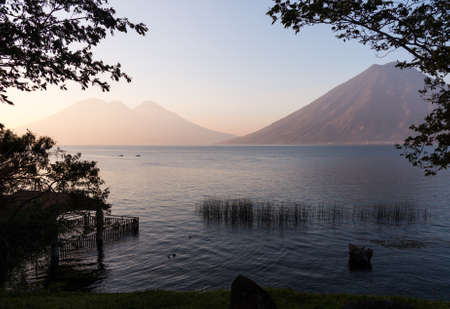 Sunrise at Lake Atitlan in Guatemala formed from volcano crater. Two small canoes are seen in the distance floating on the calm waters